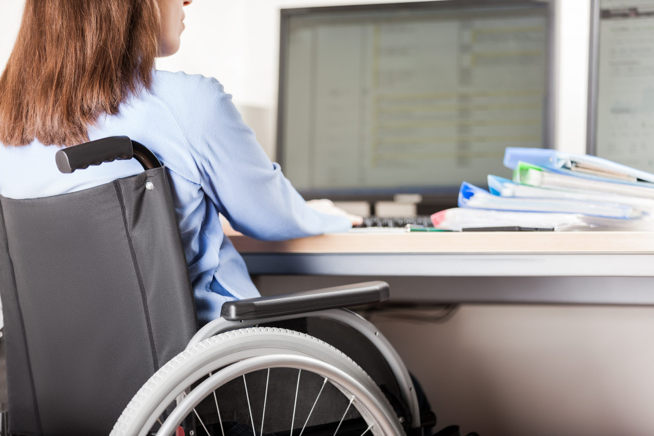 Photo of a woman in a wheelchair working at a computer desk