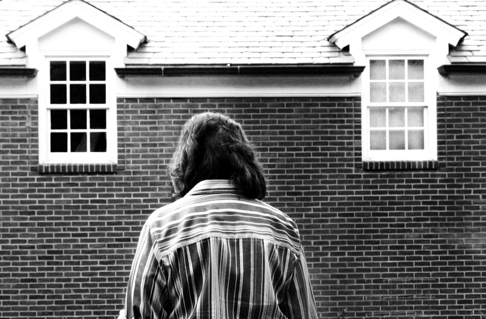 a back and white image of a woman looking down in front of a dark building.