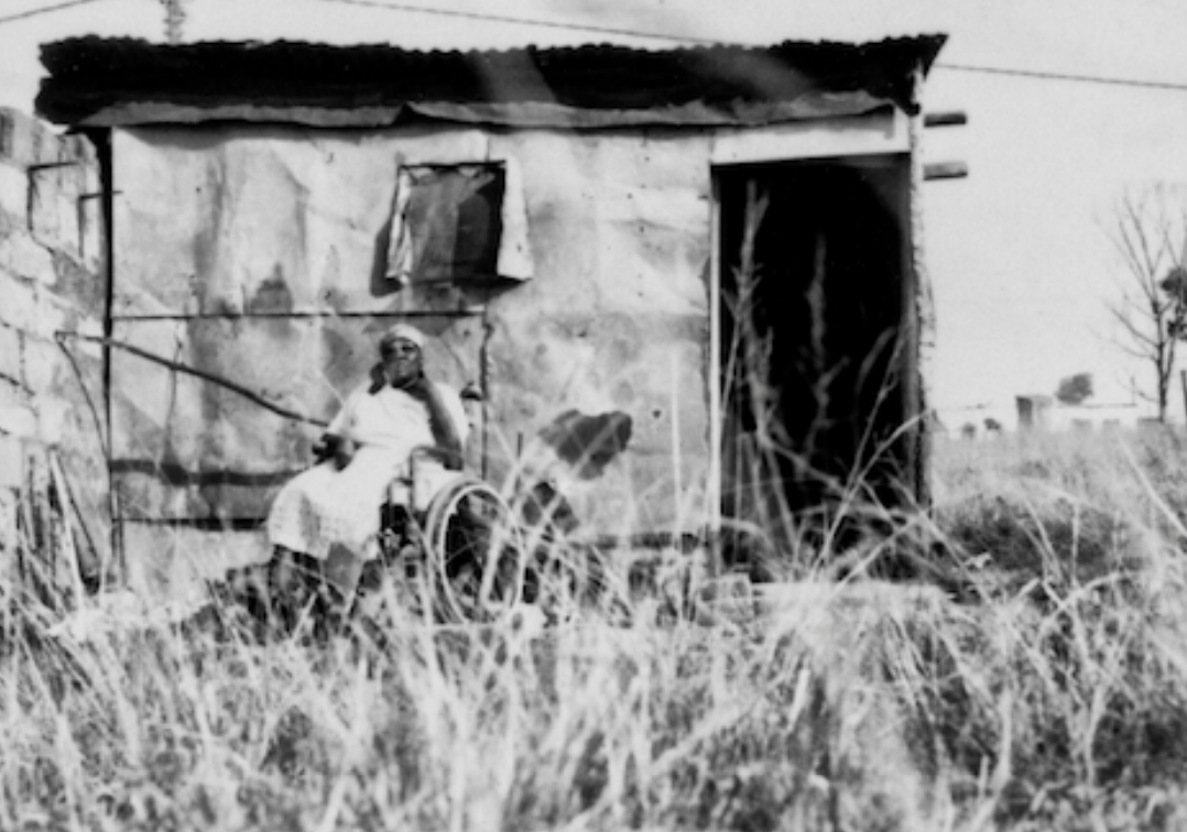 Photo of a woman in a wheelchair outside a disintegrating house.