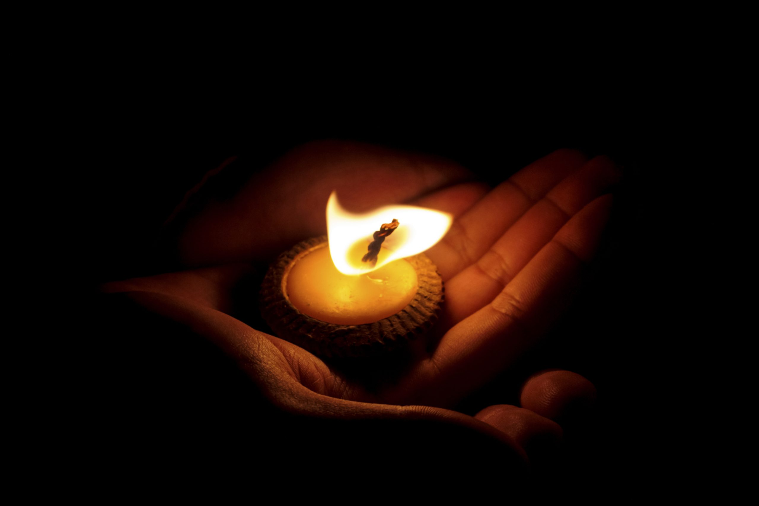 Photo of a candle sitting in the palm of a hand.