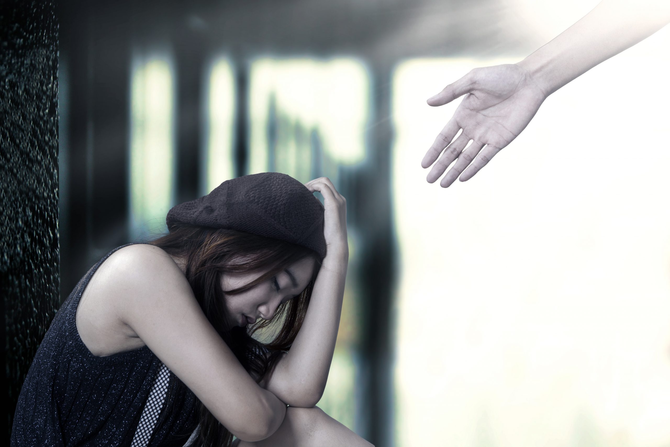 Photo of woman sitting down looking sad with someone reaching out their hand to help.