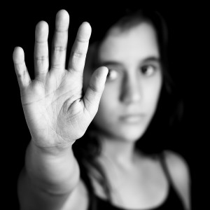 Greyscale photo of young woman putting her hand up in a stop motion.