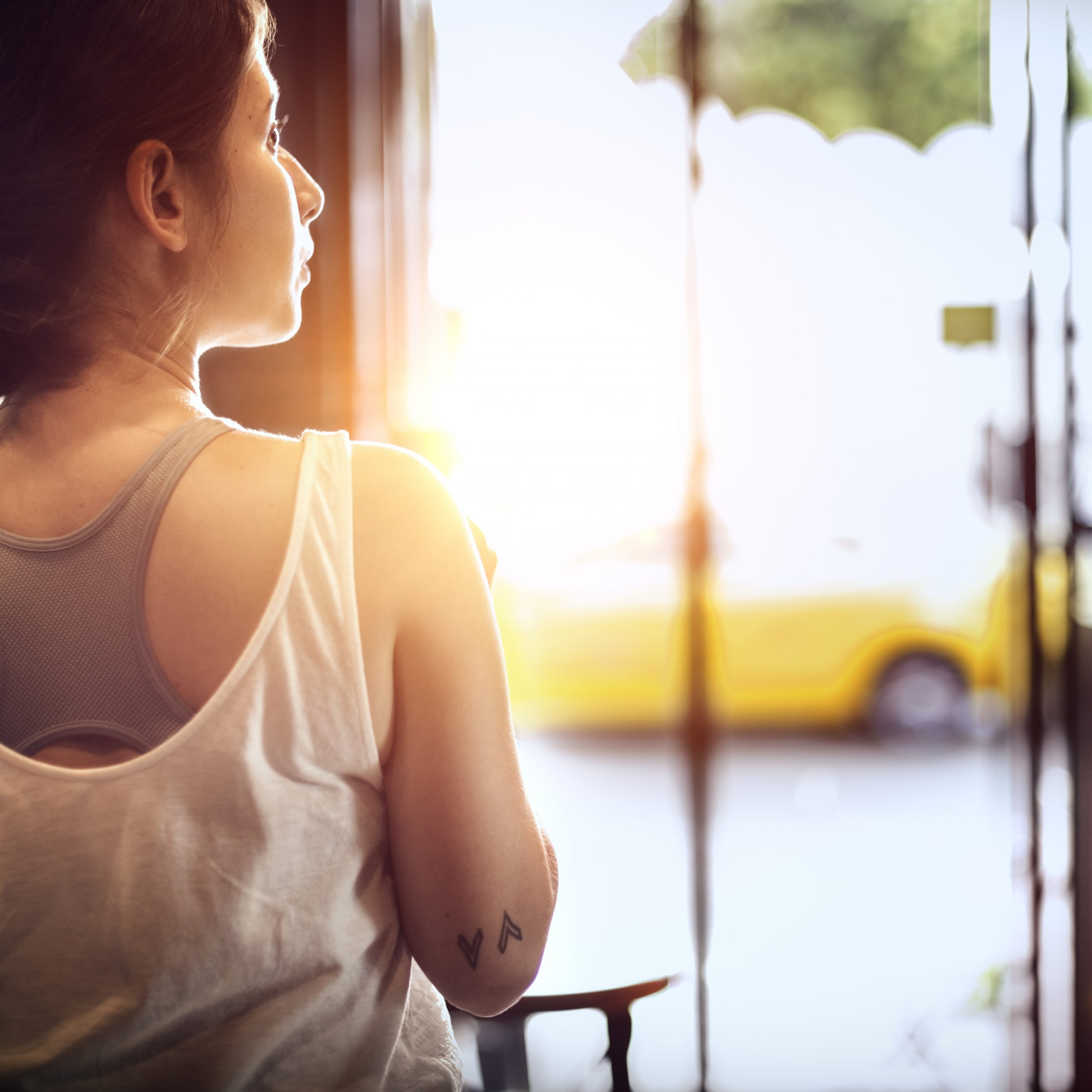 Photo of a woman looking out a window.