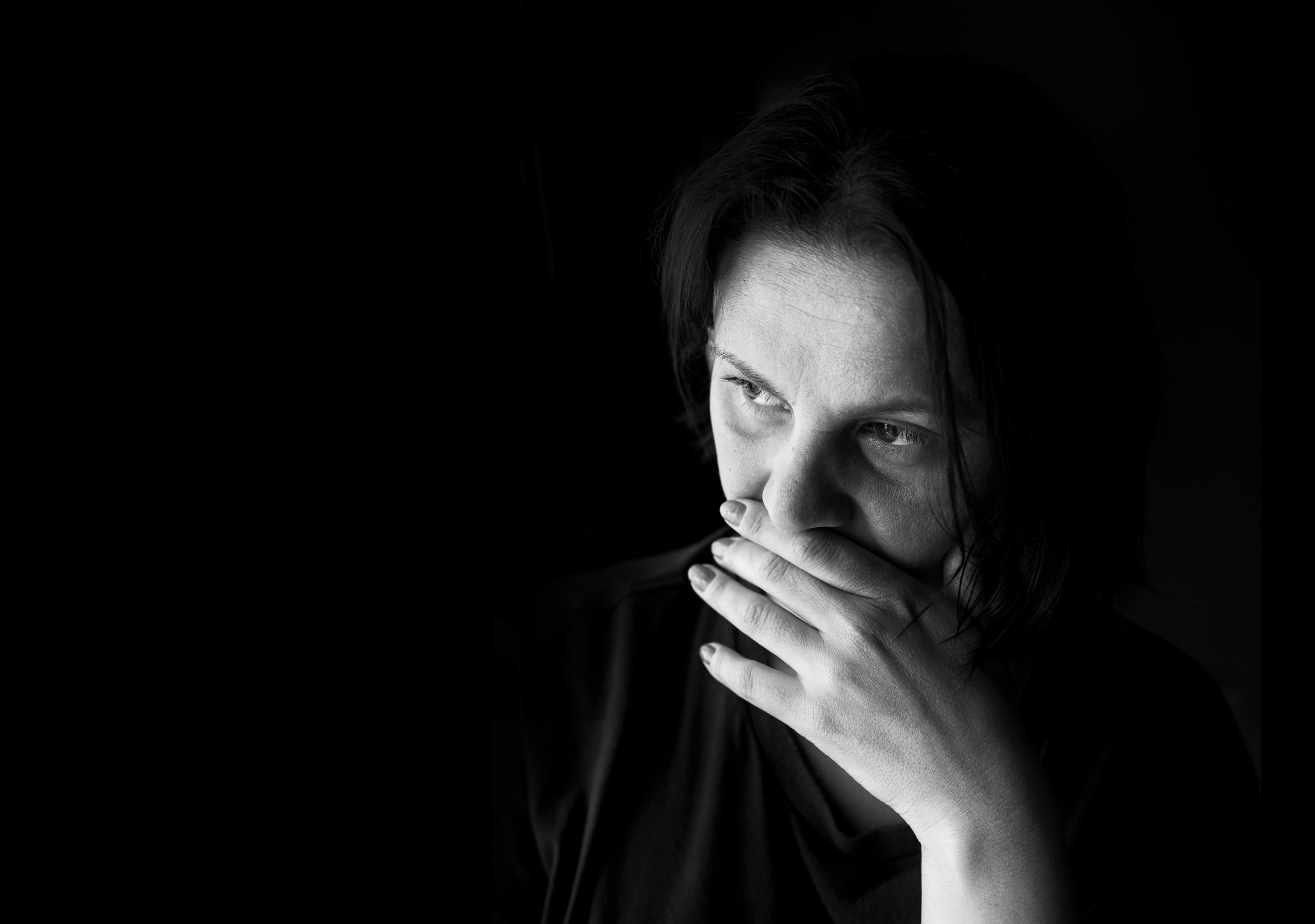 Greyscale photo of a woman with her hand to her mouth sitting in the dark.