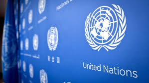 Blue wall with white United Nations logos duplicated across it.