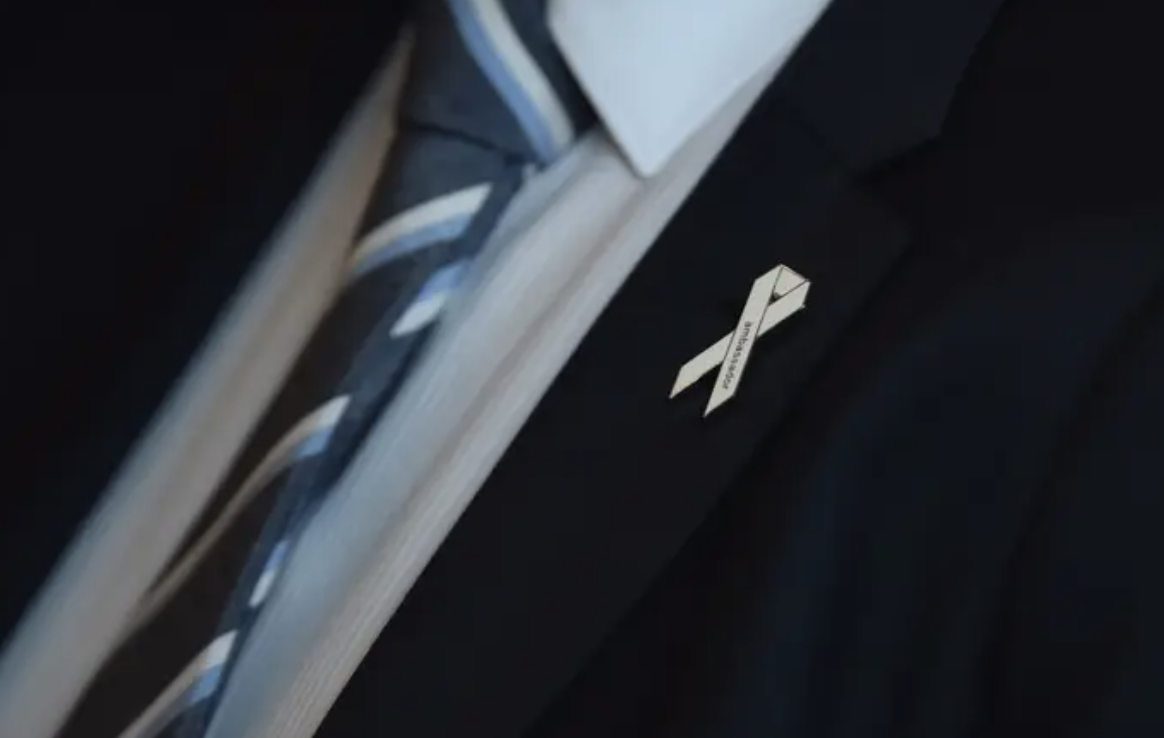 Photo of a white ribbon pinned to a mans suit jacket.