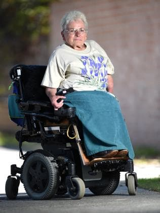 A woman with glasses and grey hair sits outside in a motorised wheelchair. She looking toward the camera with a determined expression. She wears a shirt with a violet floral print. She has a turquoise blanket draped over her legs.
