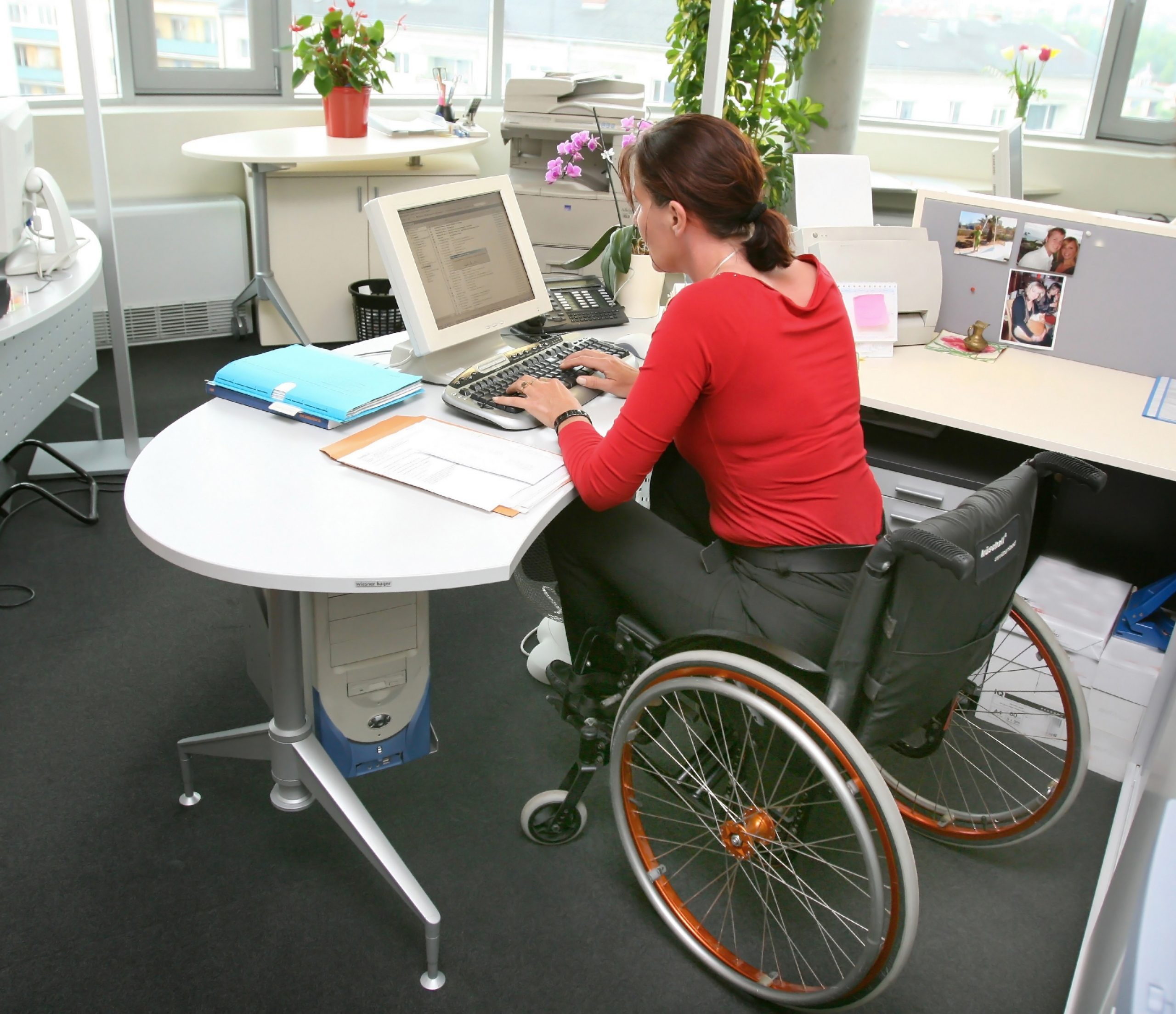 Photo of woman in a wheelchair working at a computer.