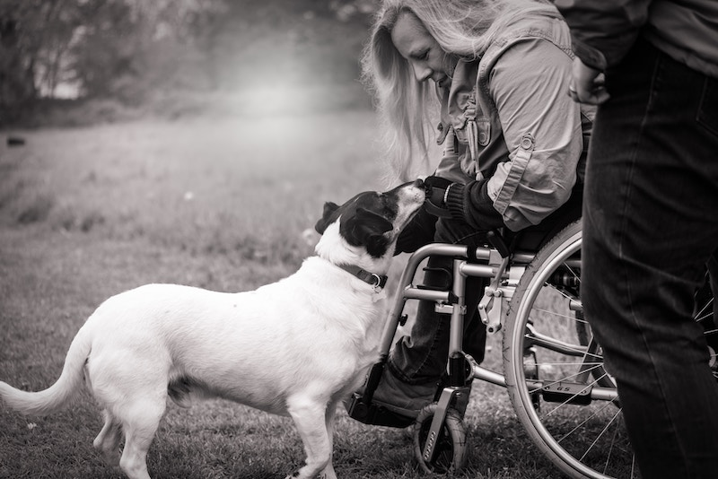 Photo of a woman in a wheelchair with a dog.