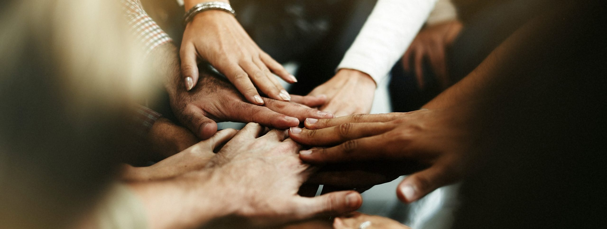 Photo of people standing in a circle and putting their hands together