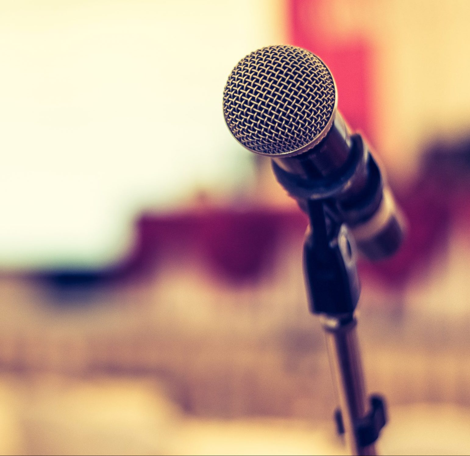 Photo of microphone with a seminar room in the background.