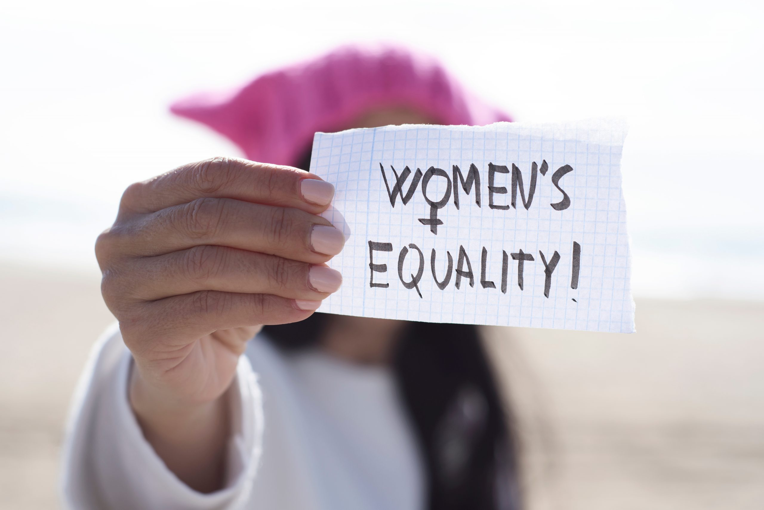 Close up of a woman holding a peice of paper with the words 'Women's Equality' on it.
