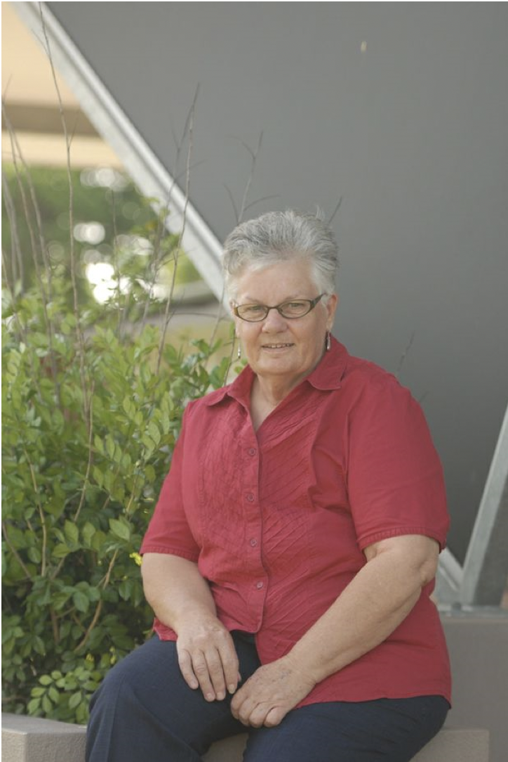 Photo of Jude Marshall, wearing a red shirt and glasses with short grey light hair.