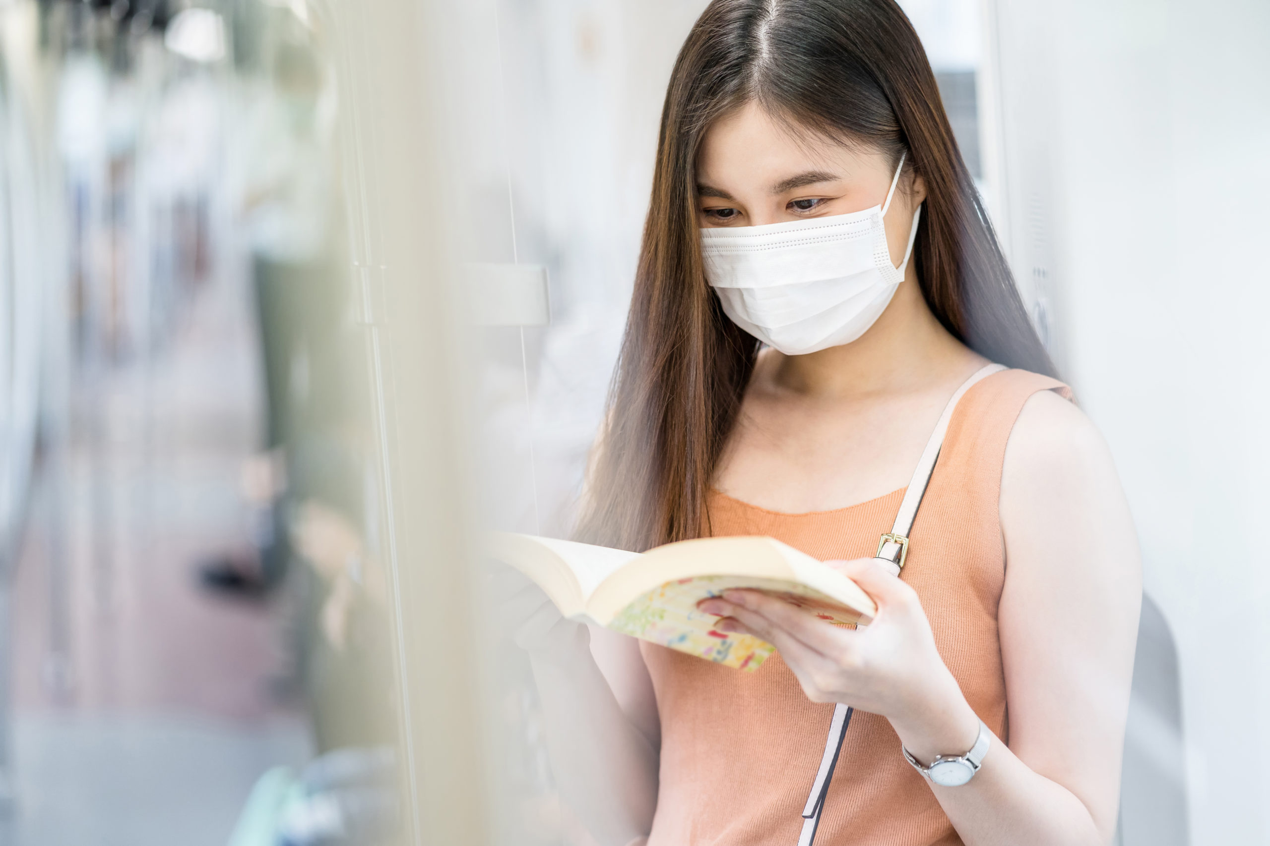 Young Asian woman passenger wearing surgical mask and reading the book in subway train when traveling in big city at Covid19 outbreak, Infection and Pandemic concept
