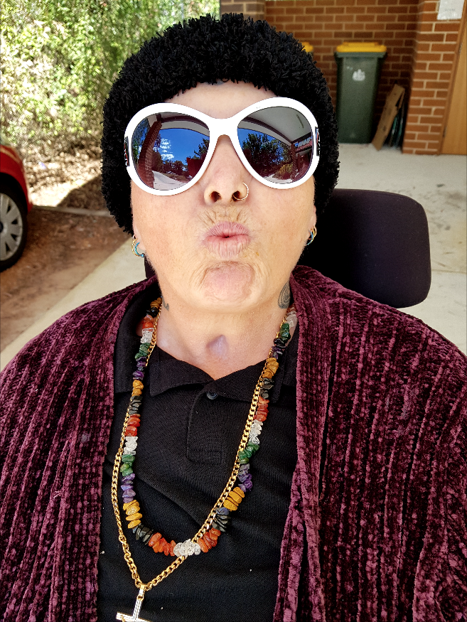 A photo of Julie, a woman wearing white sunglasses, a nose ring, a colourful necklace and a purple cardigan. She is pouting her lips and sitting in a wheelchair.