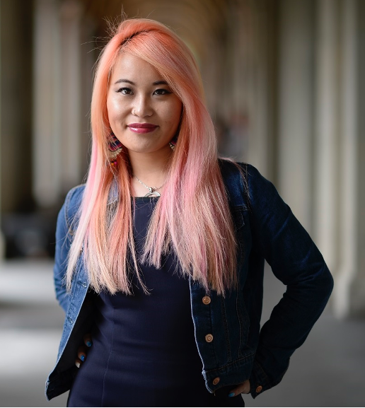 Akii Ngo (Image description a woman with long pink straight hair who is smiling. Akii is wearing a blue demin jacket and a blue top and earrings and a necklace)