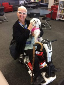 Photo of Tammy Milne cuddling a white dog wearing white glasses and red lipstick sitting in an electric wheelchair.