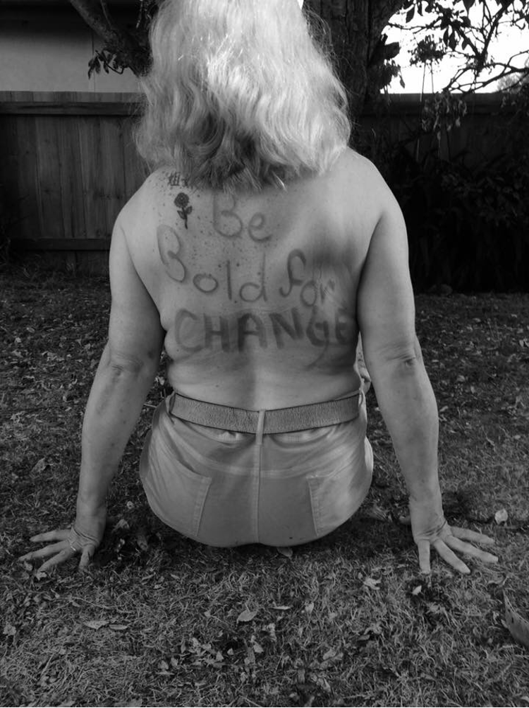 """Photo of Tammy Milne, sitting on grass, facing away from the camera with the words """"Be Bold for CHANGE"""" written in texter on her back."""