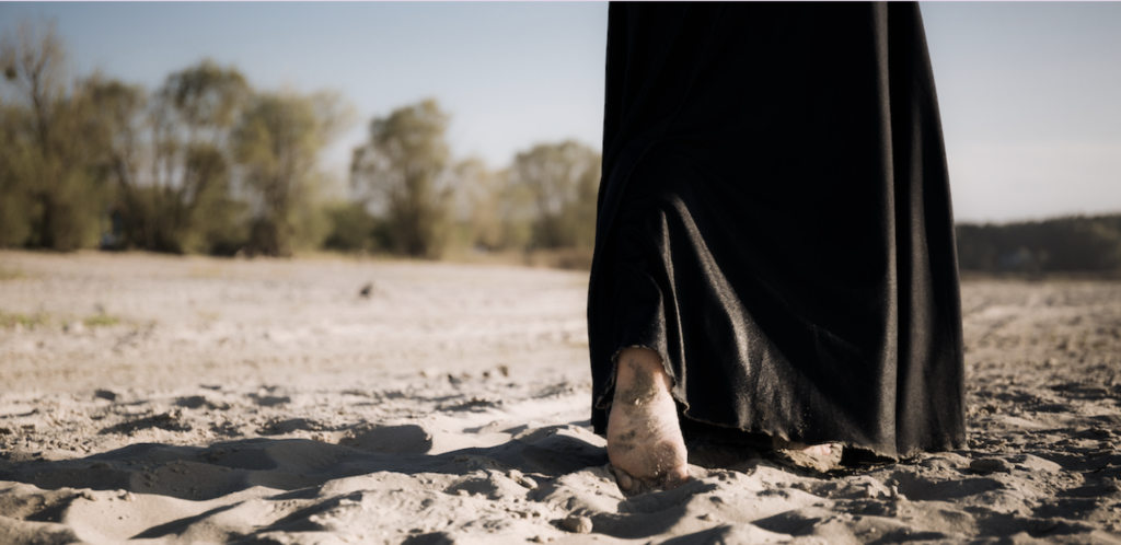 A woman with a long black dress walking on the beach