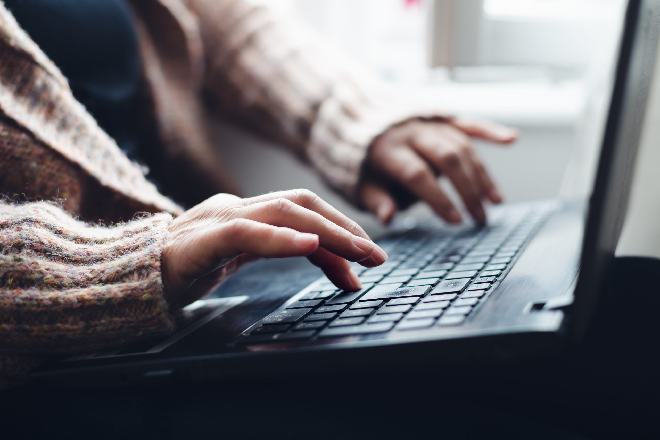 A woman working on a laptop, the photo is cropped so you can only see her hands and the laptop.