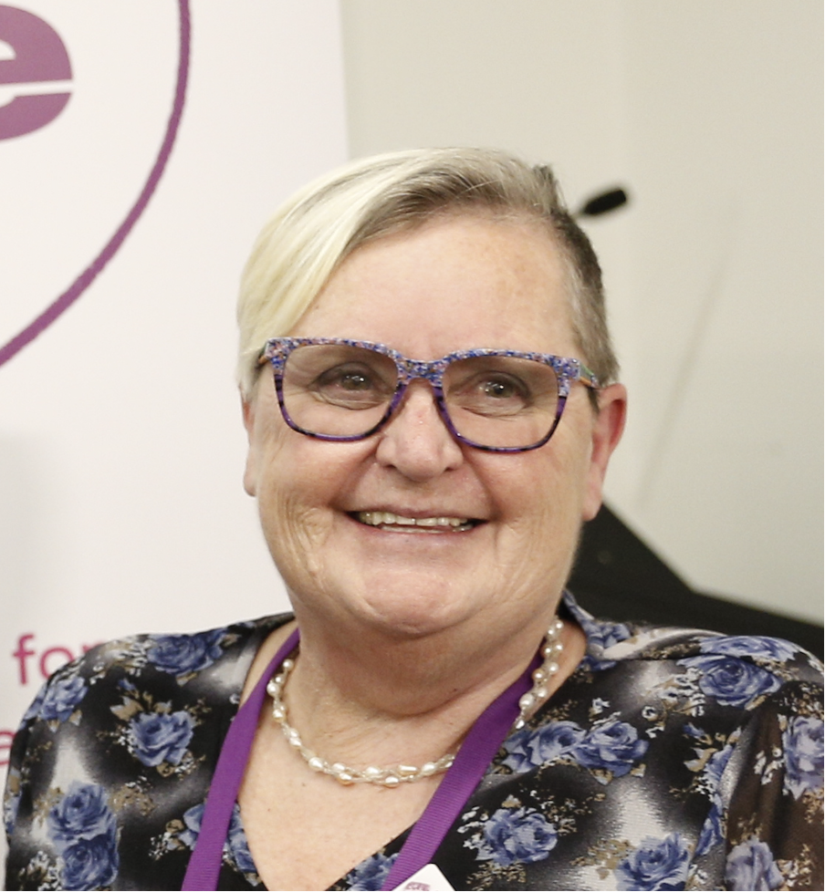 Photo of Tricia Malowney, a woman with short blonde hair and wearing purple glasses.
