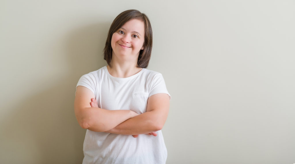 Woman with Down Syndrome wearing a white top standing against a wall smiling.