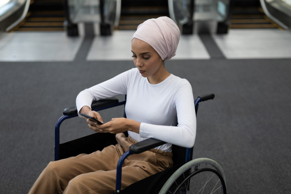 A woman sitting in a wheelchair, wearing a pink head scarf and white top, using her phone.