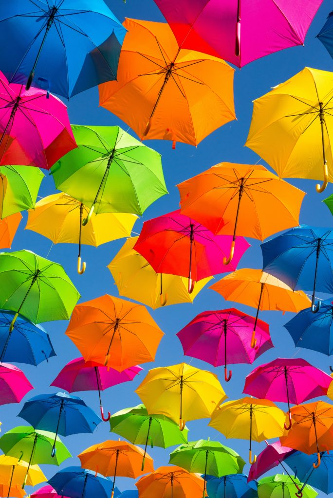 Photo source: Guy Stevens. A photo of lots of colourful umbrellas up in a blue sky.