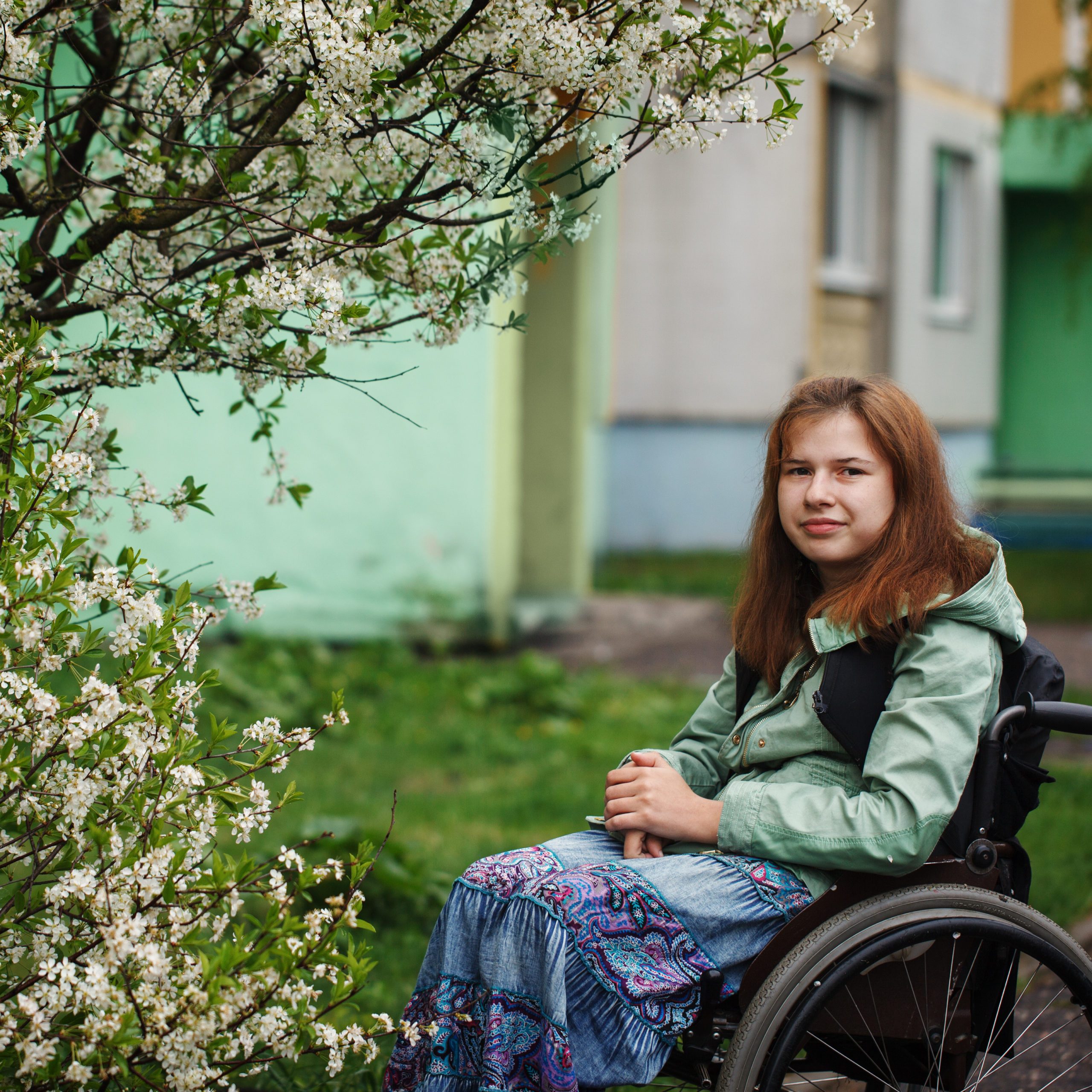 Photo of a young girlw ith brown hair sitting in a wheelchair in the garden under a blossoming tree