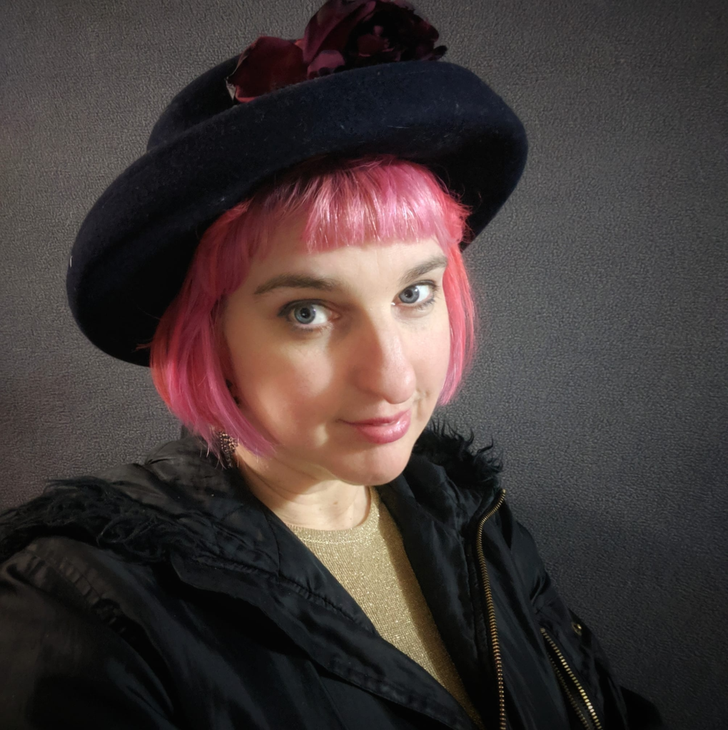 Photo of Saphia Grant who has bright pink short hair and is wearing a black hat and coat.