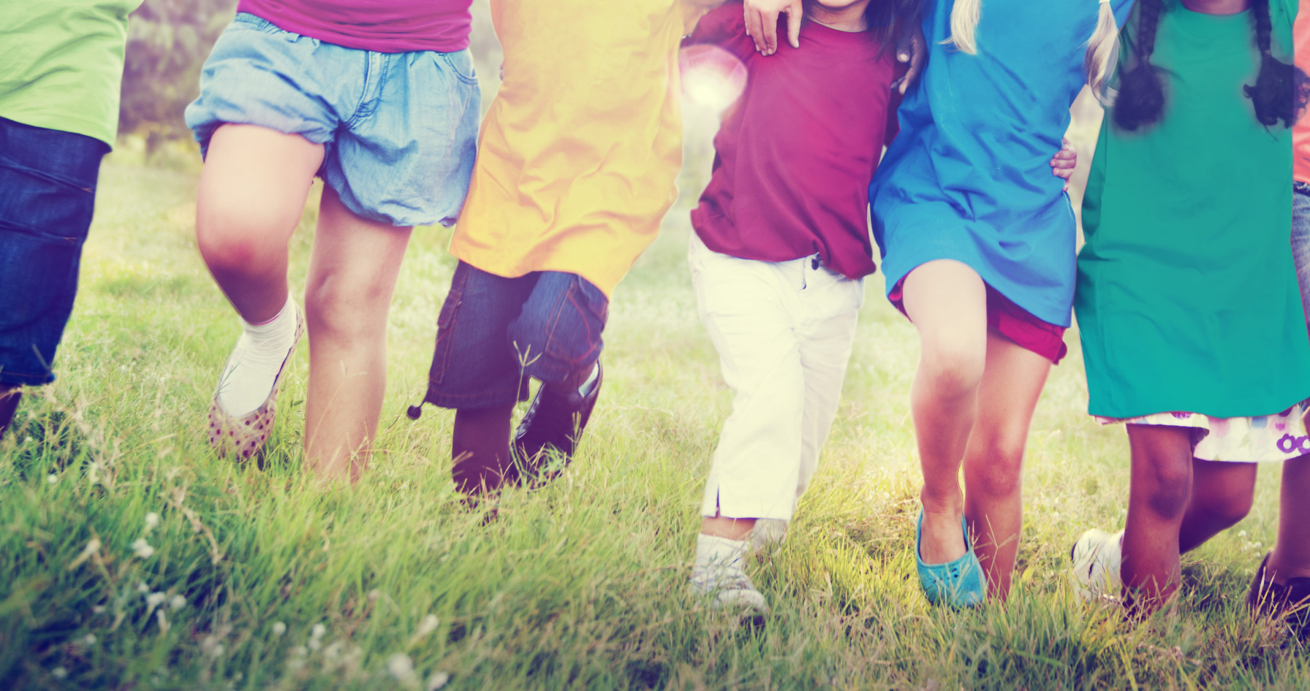 photo of a group of children linking arms and walking in a line through a field.