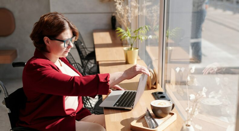 A woman wearing a white shirt and red jacket sitting at a bench in a window looking at her laptop