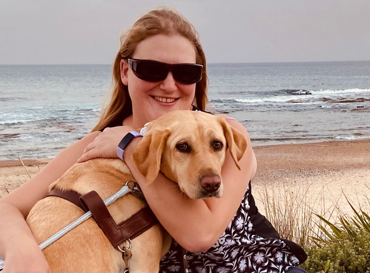 Photo of Katie who has long blonde hair and is wearing dark sunglasses. She is hugging her dog called sadie who is wearing a mobility support harness.