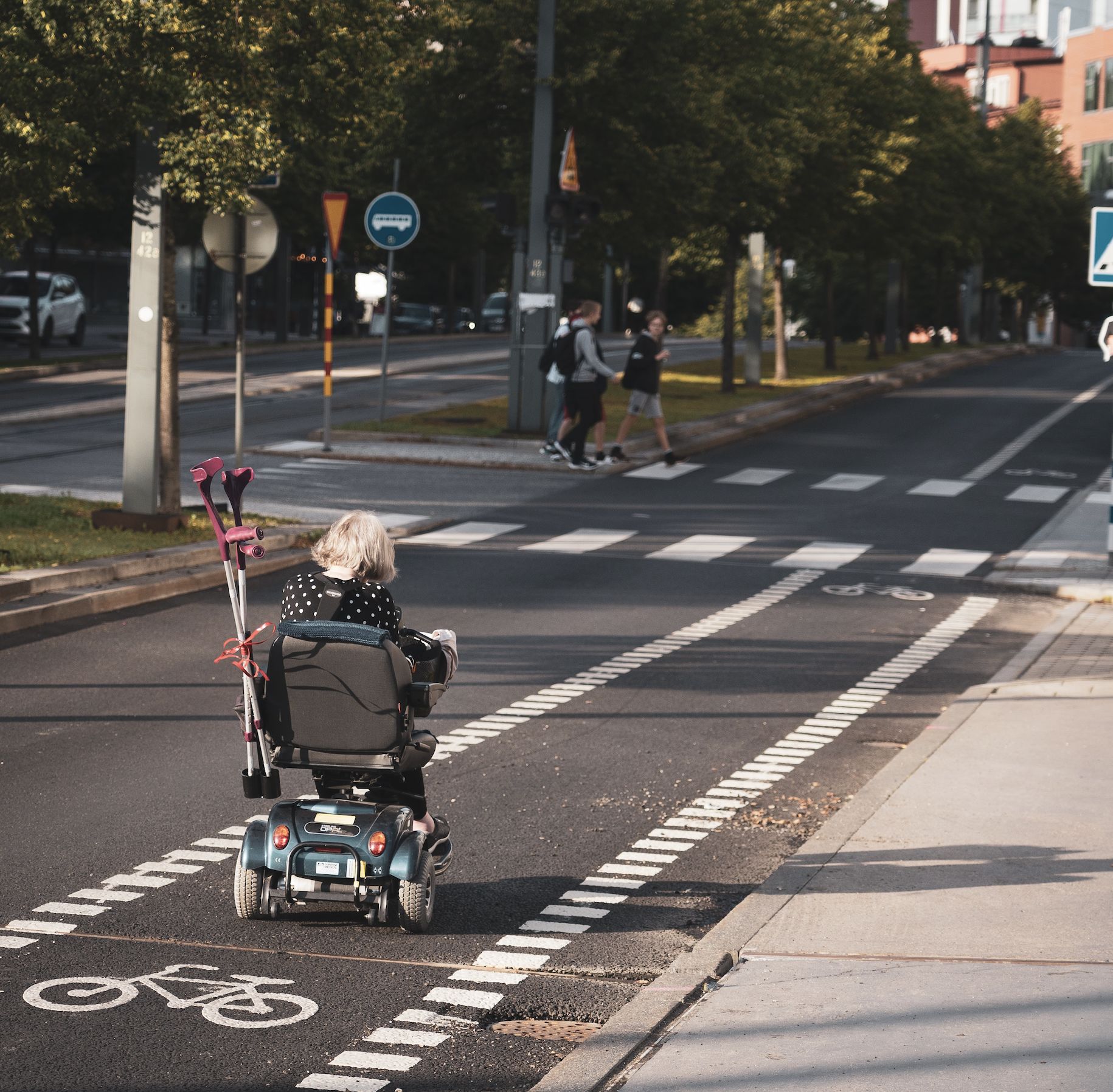 Photo of a person using a motorised wheelchair moving along a bike lane on a road