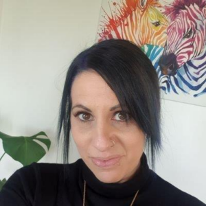 A head shot of Tess Moodie is has their hair back in a ponytail and had dark black side fringe standing in front of colourful artwork.