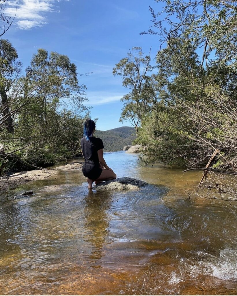 Lily, a proud Wiradjuri woman, is kneeling on rocks within a flowing creek. She is wearing all black and has her back to the camera. On either side of the creek are trees hanging overhead, and in the distance behind Lily you can see mountains.