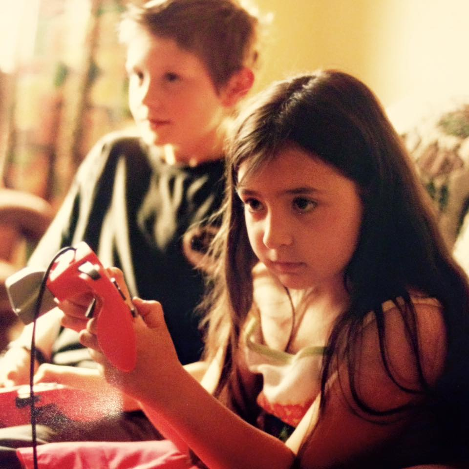 Photo of seven year old Heidi sitting on a couch with her cousin Alec, a young boy. Both Heidi and Alec are looking to the left immersed in what they are doing. They are both holding Nintendo controllers. Heidi has long dark brown hair and is wearing a white and pink dress. Her cousin in the background is wearing a black top and has short light brown hair.