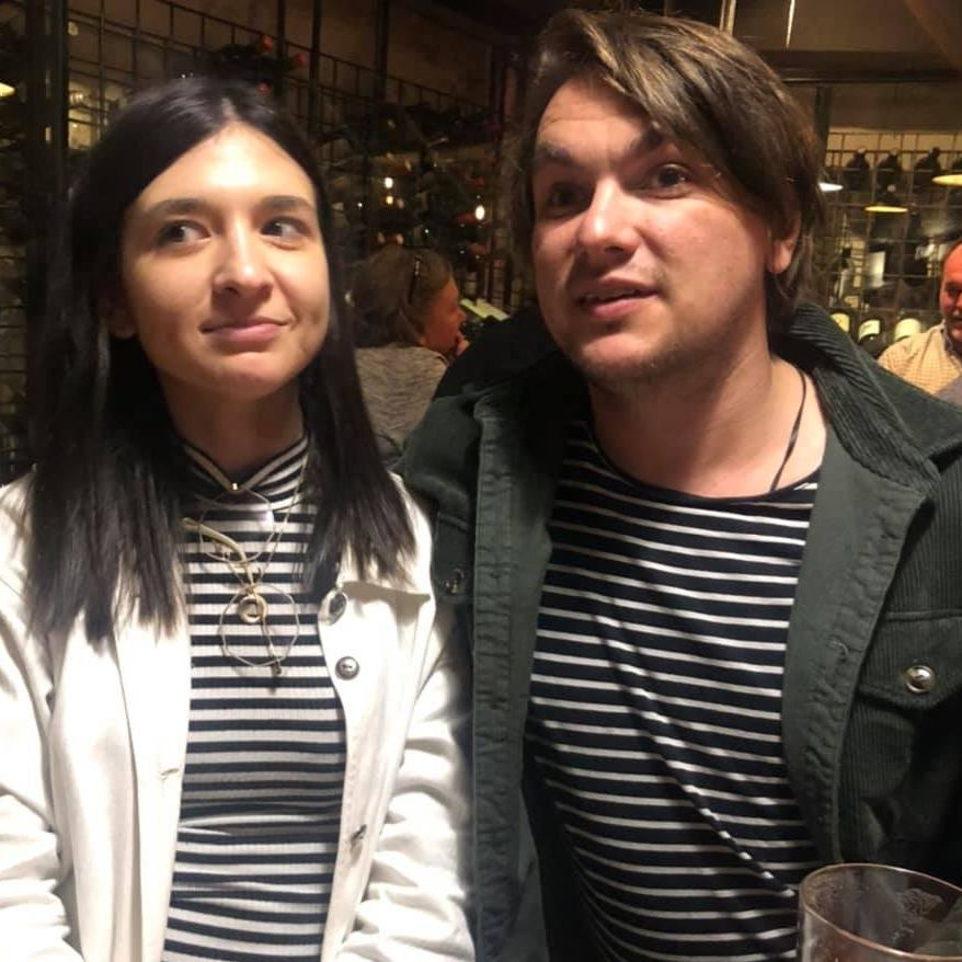 Photo of 28 year old Heidi (left) with her partner Dale (right). Both Heidi and Dale are wearing black and white stripes and looking slightly to the left. Heidi has long dark brown hair and is wearing a white jacket. Dale has short brown hair and is wearing a green jacket.