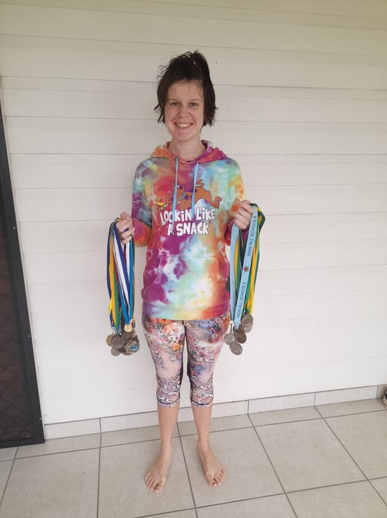 • A photo of Steph, a white woman with short brown hair, holding dozens of sporting medals. Steph is wearing a tie-dye hoodie and colourful leggings.