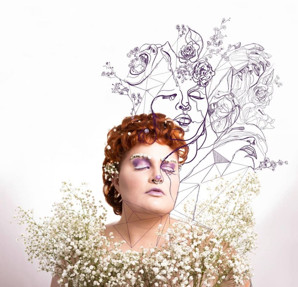 The image shows Marla, with fair skin and a curly copper mullet, with white flowers across their chest, in their hair and sitting across their brows. They are wearing purple eyeshadow and lipstick. They have their eyes closed, and on top of the photo is fine line illustrative work depicting different emotions and struggle, validating those who live with invisible illnesses.