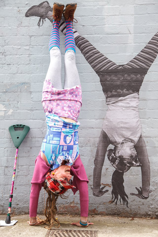 A photo of Larissa smiling and doing a handstand against a brick wall. She is wearing colourful pink and blue clothing, and has her walking stick leaning on the wall next to her. Painted on the wall is an artwork of Larissa doing a handstand!  Image credit: Larissa MacFarlane