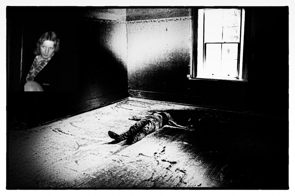 A black and white super-exposed photo of a person lying on their back on the floor, arms spread out, in the middle of a cell at the Kamballa Special Unit at Parramatta. On the wall of the room is a photo of a young woman.