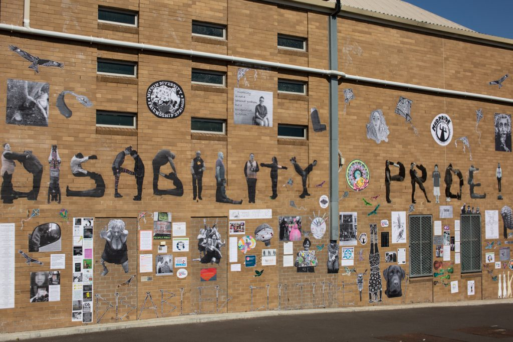 An image of the Disability Pride mural in Melbourne. It features many different pasteups on a brick wall, including the text 'Disability Pride' spelt out using images of different disabled people contorting to make the shape of letters.