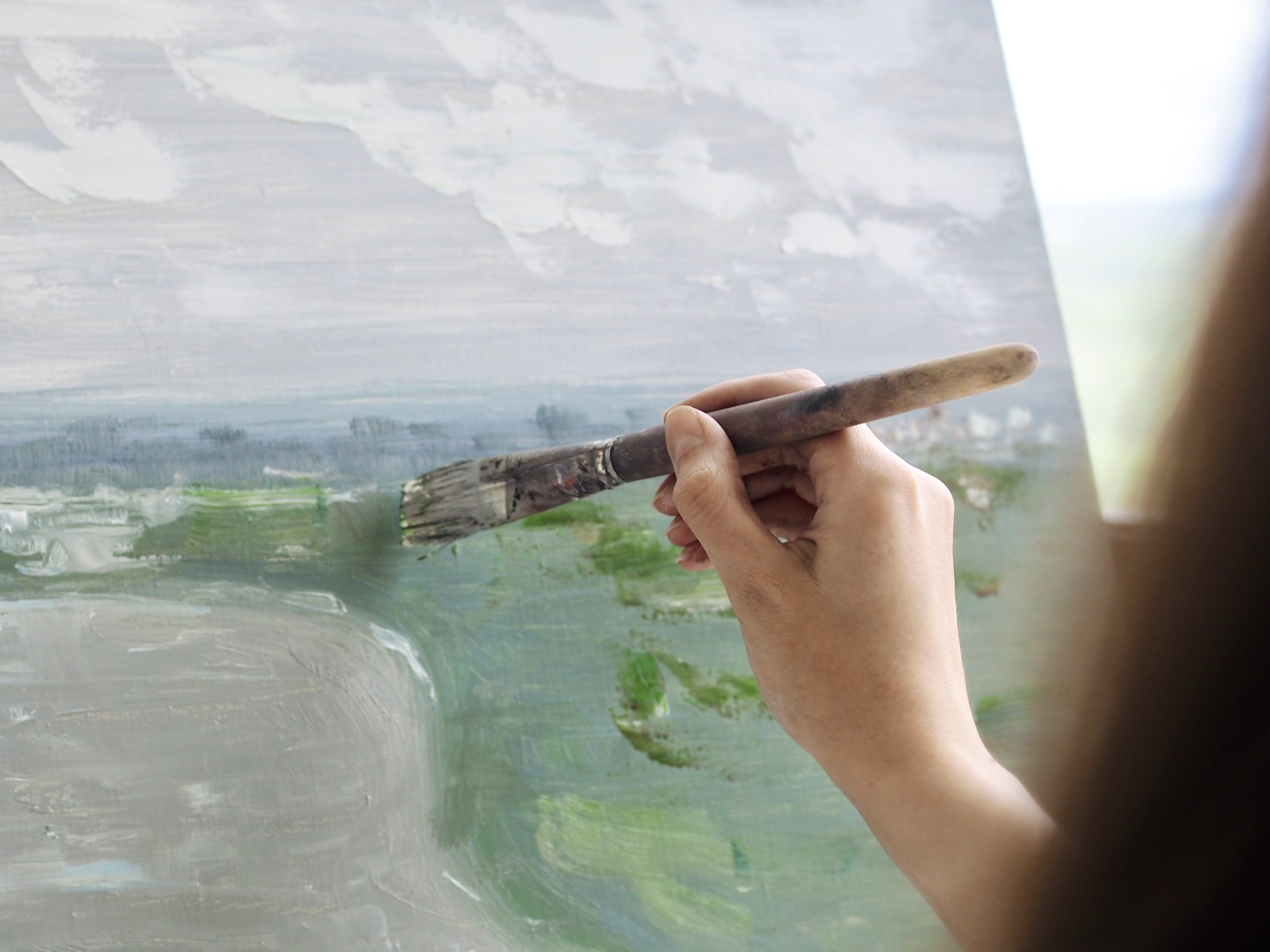 A close up photo of an artist's hand, painting an abstract oil painting in an art studio.