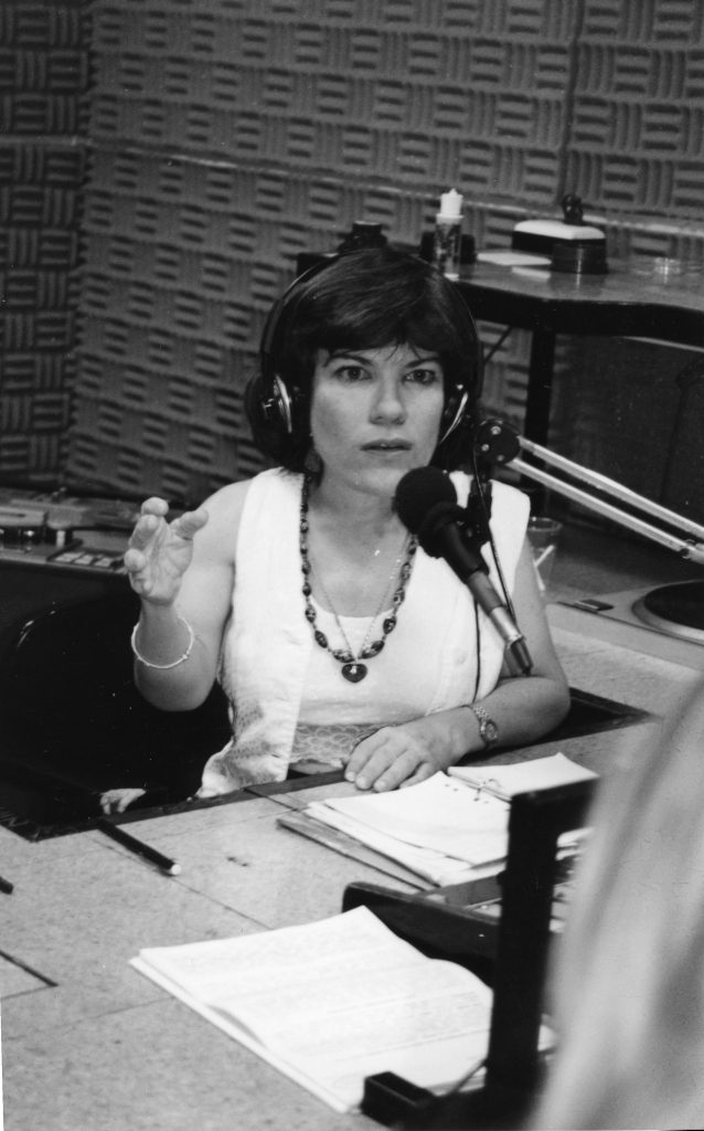 A black and white image of Suchita, a small-statured white woman with short brown hair, wearing a white shirt, chunky necklace, and black headphones. She is in a radio studio speaking into a microphone.