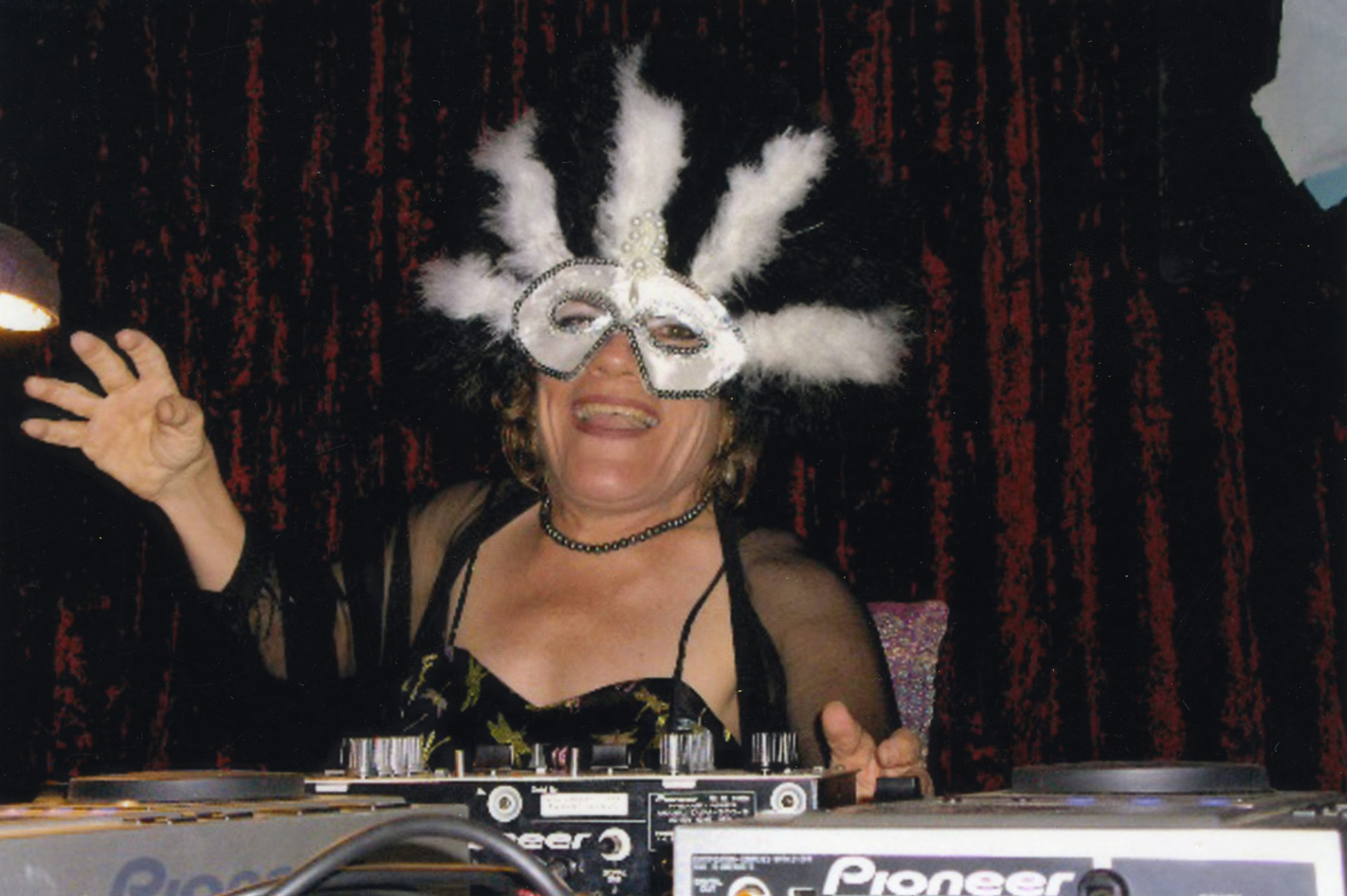 A small-statured woman wearing a black dress, see-through cardigan and white dress-up mask with feathers is smiling and laughing. She is sitting behind some DJ decks she is using at a masked-ball event.