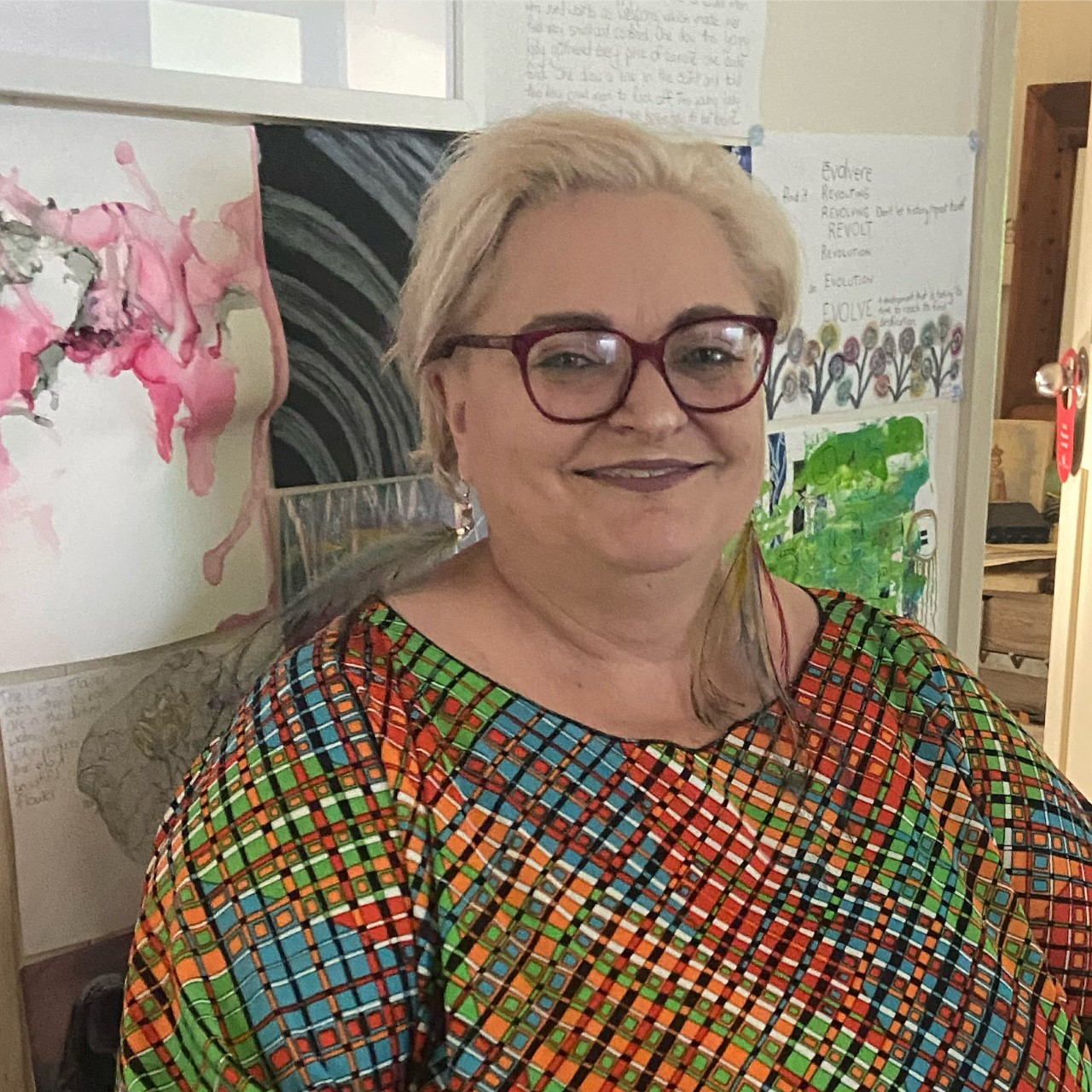 A middle aged white woman wearing pink framed glasses with short blonde hair. She is wearing a multicoloured geometrical Kaftan and standing in front of some artwork.