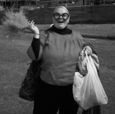 A middle aged white woman with blonde hair standing on an oval. She is wearing a top and pants with whacky glasses and holding a large feather and white plastic bag in either hand.