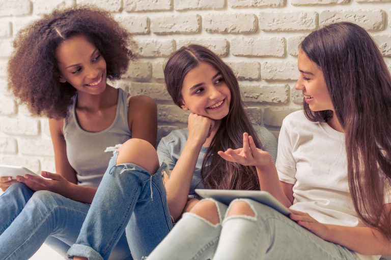 Three young women sitting against a wall talking.