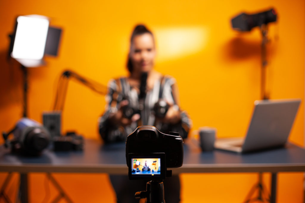 Photo of a woman doing a professional vlog.